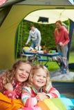 Familj som tycker om campa ferie på campingplats royaltyfria bilder
