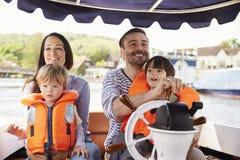 Familj som tycker om dag ut i fartyg på floden tillsammans Arkivfoton
