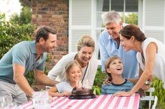 Familj som tycker om födelsedagpartiet arkivfoton
