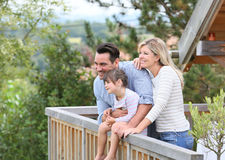 Familj som tycker om ferier i träkabin Arkivbild