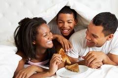 Familj som tycker om frukosten i säng Arkivfoto