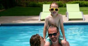 Familj som tycker om i simbassäng arkivfilmer