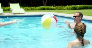 Familj som tycker om i simbassäng stock video