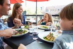 Familj som tycker om mål på den utomhus- restaurangen royaltyfria bilder