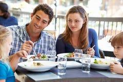 Familj som tycker om mål på den utomhus- restaurangen arkivfoton