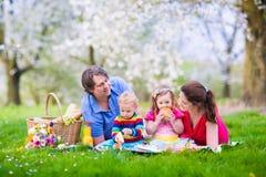 Familj som tycker om picknicken i blommande trädgård royaltyfri bild