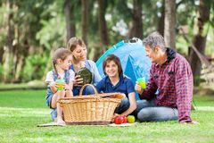 Familj som tycker om picknicken på campingplatsen arkivbild