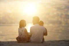 Familj som tycker om solnedgångsikt Arkivbild