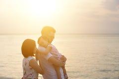 Familj som tycker om sommarferie på stranden Arkivbild