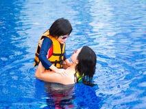Familj som tycker om sommarsemester i lyxig simbassäng royaltyfria foton