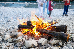 Familj som tycker om tid vid floden och dengjorda lägerelden Royaltyfri Foto