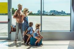 Familj som ut ser fönstret i flygplats royaltyfri foto