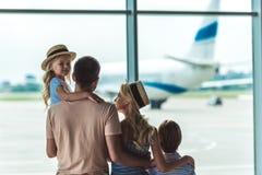Familj som ut ser fönstret i flygplats arkivfoton