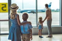 Familj som ut ser fönstret i flygplats royaltyfria foton