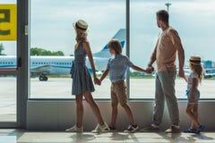 Familj som ut ser fönstret i flygplats royaltyfri fotografi