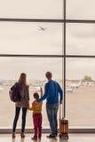 Familj som ut ser fönstret på flygplatsen arkivfoto