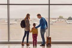 Familj som ut ser fönstret på flygplatsen Arkivfoton