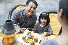Familj som utanför delar och äter kinesisk mat royaltyfri foto