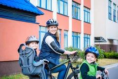 Familj som utomhus cyklar, fader med den lyckliga ungeridningcykeln Royaltyfria Foton