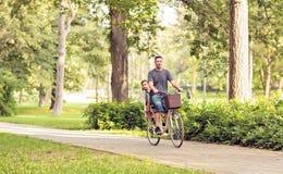 Familj som utomhus cyklar - familjen på cyklar parkerar in royaltyfri bild