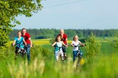 Familj som utomhus cyklar i sommar Royaltyfri Bild