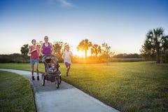Familj som utomhus joggar och tillsammans övar royaltyfri foto