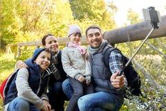 Familj som utomhus tar fotoet vid selfiepinnen royaltyfri fotografi