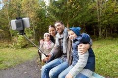 Familj som utomhus tar fotoet vid selfiepinnen arkivbild