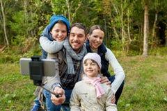 Familj som utomhus tar fotoet vid selfiepinnen arkivfoton