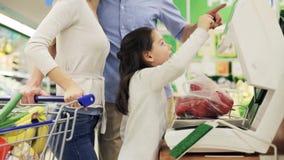 Familj som väger paprika på skala på livsmedelsbutiken arkivfilmer