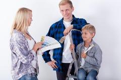 Familj som väljer färger för att måla fotografering för bildbyråer