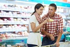 Familj som väljer mat på shopping i supermarket Arkivfoto