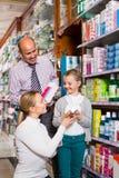 Familj som väljer objekt i apotek royaltyfri foto