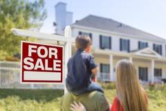 Familj som vänder mot det till salu det Real Estate tecknet och huset Arkivfoto