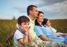 Familj som vilar tillsammans att sitta p? gr?s i natur arkivbilder