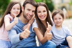 Familj som visar upp tum Fotografering för Bildbyråer