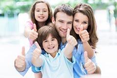 Familj som visar upp tum arkivbild