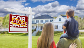 Familj som vänder mot det sålda till salu Real Estate tecknet och huset Arkivbild