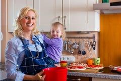 Familj - stekhet pizza för moder och för barn Royaltyfria Bilder