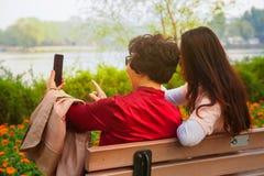 Familj, teknologi och folkbegrepp - den lyckliga dottern och den h?ga modern med smartphonen som sitter p?, parkerar b?nken och a arkivbilder