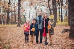 Familj tre barn i skogen som blir i höstsidorna arkivfoto