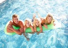 familj utanför avslappnande simning för pöl Arkivfoto