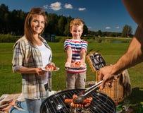 Familj utomhus på picknick Fotografering för Bildbyråer