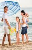 Familjanseende under solparaplyet arkivbilder