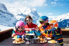 Familjapres skidar lunch i berg Skida gyckel arkivbild