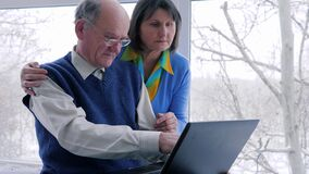 Familjatmosfär, gamla människor arbetar med datoren på internet inomhus stock video