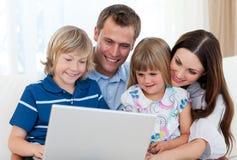 familjbärbar dator som ler genom att använda Royaltyfri Fotografi