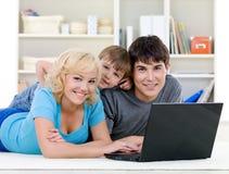 familjbärbar dator som ler genom att använda Royaltyfria Foton