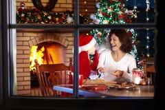 Familjbakning på jul Modern och barnet bakar arkivbild
