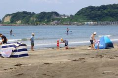 Familjbarn som spelar langa strandhavet, Kamakura, Japan Arkivfoto